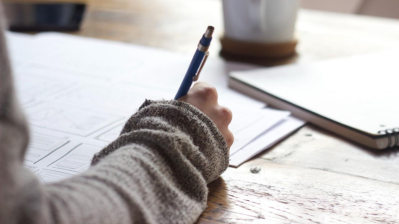 Eine-Frau-sitzt-am-Tisch-und-schreibt-mit-einem-Kulli-auf-einem-Block