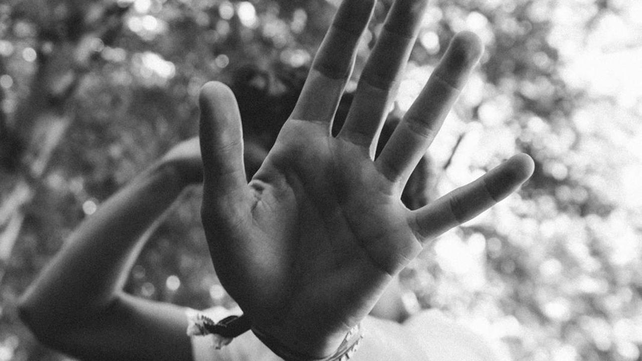 Frau-verdeckt-mit-ihrer-Hand-die-Kamera