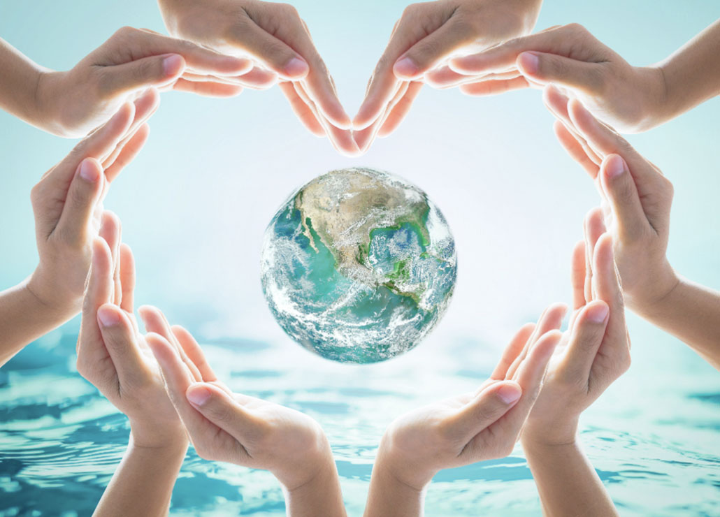 Weltkugel-umgeben-von-Haenden-ueber-Wasser-in-Herzform